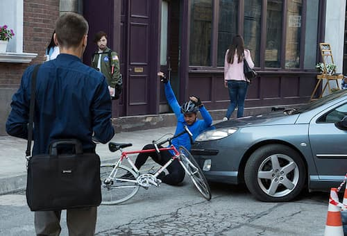 Man on a bicycle being hit by a car